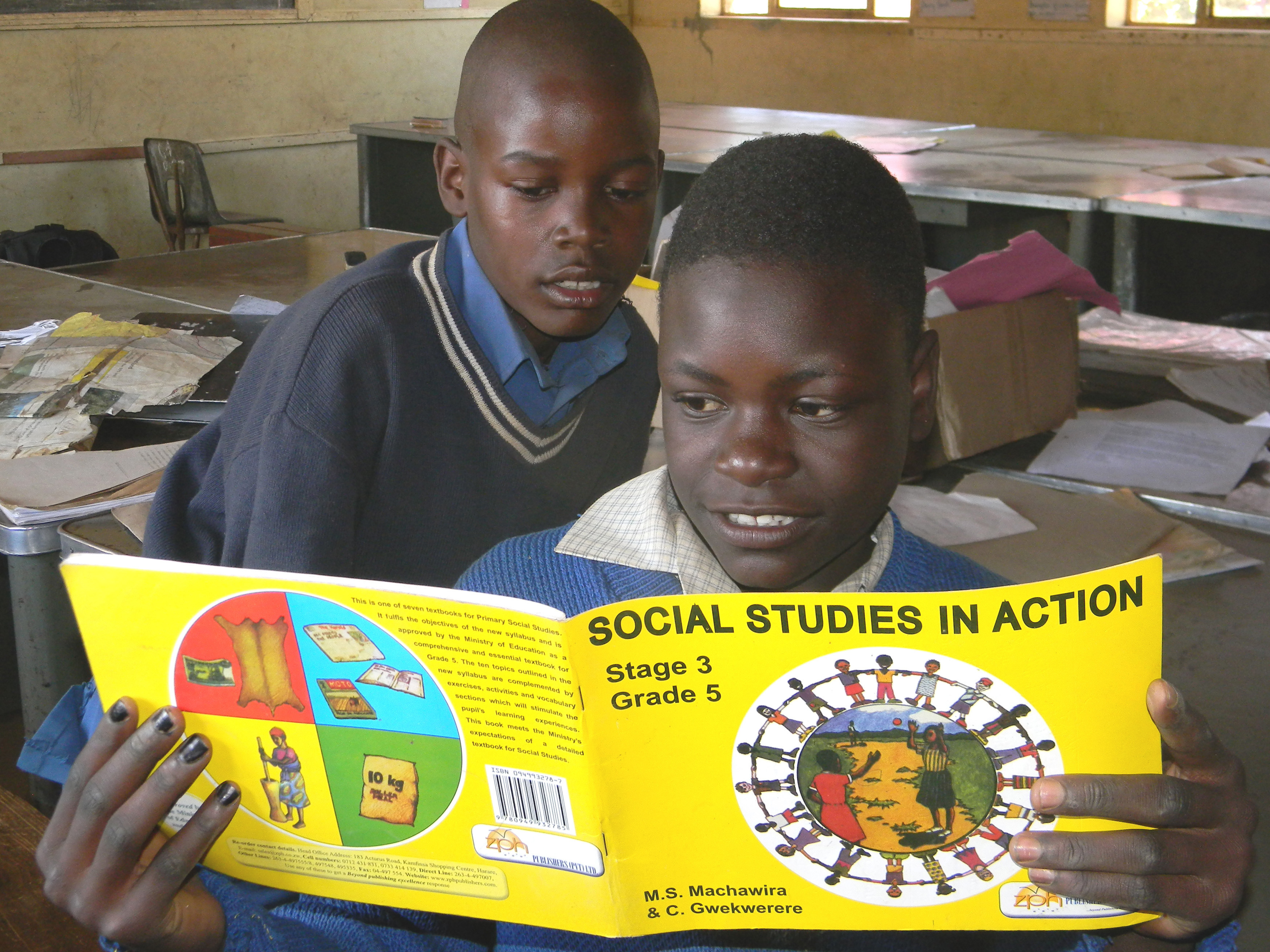 Harare, Zimbabwe, October 18 2015. Primary school children reading a Social Studies book inside a classroom. Social studies is one of the important subjects at primary school.
