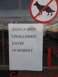 Sign on door saying immigrants unallowed entry in market